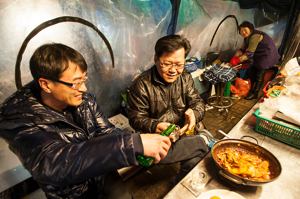 Friends share soju and a spicy seafood stew at a pojangmacha in Nampo-dong, Busan, South Korea.