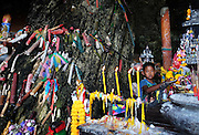 A young boy looks out from the Phra Nang Cave also known as the Princess Cave. Since ancient times fisherman have brought offerings to the Phallus of Shiva in return for hopes of protection and a good catch from the ocean.