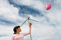 Girl (7-9) playing with balloon at wind farm