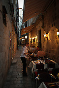 Restaurant worker tends to tables out in the street of Dubrovnik, Croatia