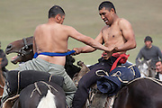 Horseback wrestling competition (Er-Enish) at a traditional Kyrgyz horse games festival. Bosogo jailoo, Naryn province, Kyrgyzstan.