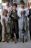 Pakistan   1986..A Pakistani tribal  Boys with  Rifle..Darra Adamkhel is Pakistan's largest weapons bazaar and factory, renowned for its gun making expertise since the late 19th century, Darra is a sprawl of hundreds of workshops where some 3,500 gunsmiths toil on replica weapons.