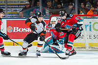 KELOWNA, BC - NOVEMBER 8:  Elijah Brown #5 of the Medicine Hat Tigers moves the puck around Kaedan Korczak #6 for a shot on Roman Basran #30 of the Kelowna Rockets during first period at Prospera Place on November 8, 2019 in Kelowna, Canada. (Photo by Marissa Baecker/Shoot the Breeze)