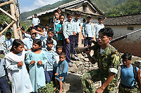 Members of the People?s Liberation Army, the Maoist rebels that control large parts of rural Nepal, walk by a school in a remote part of western Nepal on June 21, 2006. The ten-year old conflict in Nepal has claimed an estimated 13,000 lives. (Photo/Scott Dalton)