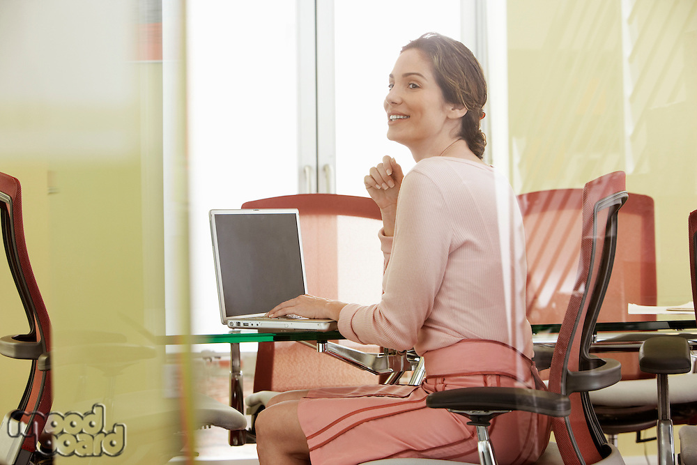 Woman using laptop in conference room