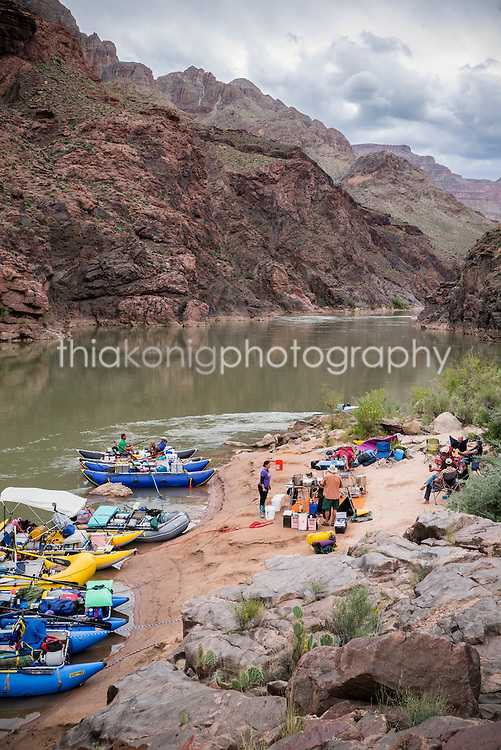 Rafts and camp on the banks of the Colorado River with looming rain clouds, Grand Canyon, AZ