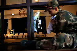 Chinese soldiers clean the windows of a meeting room in a building known as the 'Water Dripping Cave' where Mao Zedong stayed briefly for 11 days in 1966 and is thought to have contemplated the start of the Cultural Revolution there in Shaoshan, Hunan Province in central China, 28 April 2016. The seat lighted with a lamp is known as Mao's seat in the meeting room. Shaoshan is the hometown of former Communist leader Mao Zedong, popularly known as Chairman Mao. Thousands of visitors descend on this small Chinese town burrowed in the hills of Central China's Hunan province to pay homage to the great helmsman everyday. It is one of the core sites of the 'Red Tourism' industry, where communist party cadres and ordinary Chinese tourists alike seek to relive the experiences and rekindle the spirit of the revolutionaries.