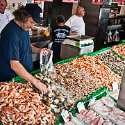 Fishmonger selling shrimp and squid at the Maine Avenue Fish Market in Washington DC.