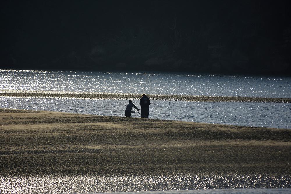 2 men fishing on the sands at sunset in Raglan