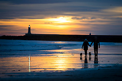 © Licensed to London News Pictures. 25/12/2015. Tynemouth, UK. Dog walkers enjoy sunrise on Christmas day on Longhands beach in Tynemouth, north east England. Photo credit: Ben Cawthra/LNP