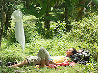 Young woman lying in tropical forest sunbathing