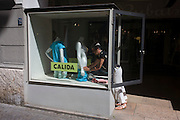 A shop assistant adjusts the clothing on a mannequin in the northern Italian south Tyrolean city of Bozen-Bolzano.