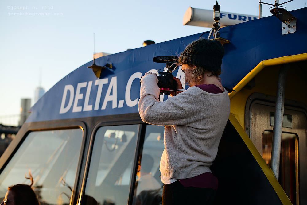 Woman using video camera on ferry, New York, NY, US