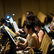 June 3, 2014 - New York, NY : Composer Wang Lu, foreground center, goes over her music during a break in rehearsal as the New York Philharmonic performs works by up-and-coming composers at Avery Fisher Hall on Tuesday. Three works by little-known composers, such as Lu, will be selected for inclusion in the New York Philharmonic's Biennial. CREDIT: Karsten Moran for The New York Times