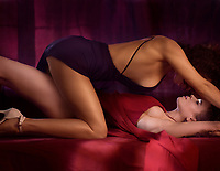 Romantic sensual photo of a sexy lesbian couple making love on a bed, two beautiful women in blue and red dresses, one on top of another about to kiss