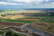 Nederland, Noord-Brabant, Werkendam, 23-10-2013; Ruimte voor de Rivier project Ontpoldering Noordwaard, rivier de Nieuwe Merwede links aan de horizon. De polder waar boerderijen en particuliere huizen op nieuw opgeworpen terpen gebouwd worden.<br /> Voor dit project worden delen van de polder ontpolderd en de dijken worden verlegd en/of verlaagd waardoor bij hoogwater het rivierwater ook door de polder sneller weg kan stromen richting zee. Gevolg van de ingrepen is ook dat de waterstand verder stroomopwaarts zal dalen.<br /> National Project Ruimte voor de Rivier (Room for the River) By lowering and / or moving the dike of the Noordwaard polder the area will become subject to controlled inundation and function as a dedicated water detention district. Houses and farmhouses will be constructed on new dwelling mounds. <br /> luchtfoto (toeslag op standard tarieven);<br /> aerial photo (additional fee required);<br /> copyright foto/photo Siebe Swart