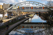 A London Overground train crosses on a bridge over the Regent's canal in Dalston, London, United Kingdom.  This overland line has recently been developed and connects East London with South London.  The canal flows from East London to West London.