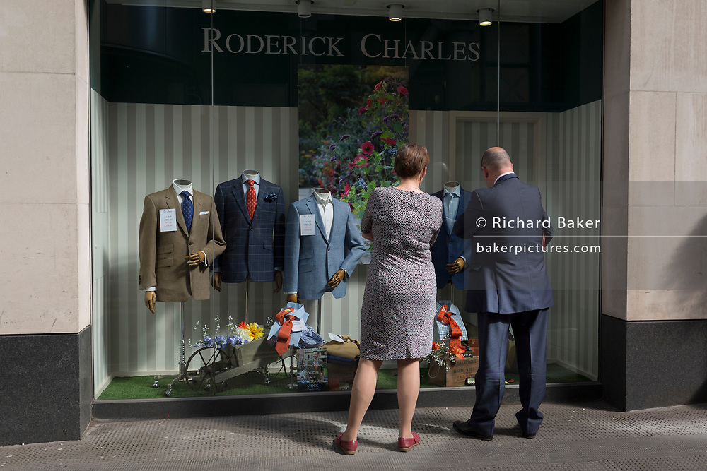 A man and woman look at the display of a menswear outfitters  in the City of London, the capital's financial district aka the Square Mile, on 17th May 2018, in London, UK.