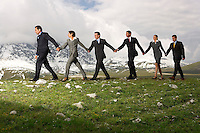 Business People Holding Hands and Walking through mountains side view