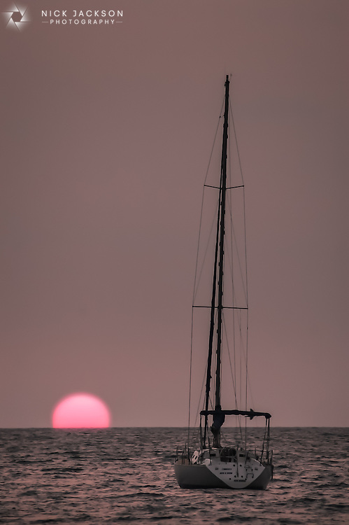 A saiboat heads towards the sun as it dips into the ocean just off Hermosa Beach on the Costa Rican coast