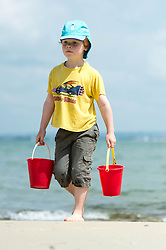 © Licensed to London News Pictures. 14/06/2014. Ryde, Isle of Wight, UK. A child carries buckets of seawater from the sea on a hot sunny morning.  The UK is experiencing a period of hot sunny weather with temperatures over the weekend expected to reach 74 F (23 C).  Photo credit : Richard Isaac/LNP