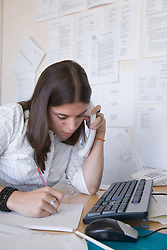 Young woman sitting at her desk talking on the phone,