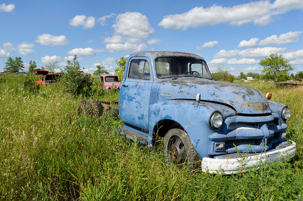 Blue Pickup Truck in Junkyard Under Summer Skies   Dierks Photo