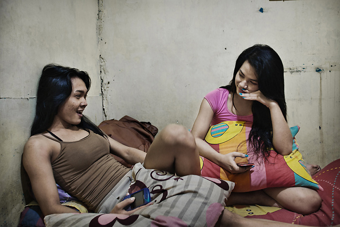 JAKARTA, INDONESIA, MARCH 2013: Gea (right), the youngest one in the house, joking with her friend in the bedroom she shares with another young transgender at Mami Joyce's house. Being the youngest one in the &quot;family&quot;, she can easily earn up to 700.000 rupiahs (70$) on an average saturday night. <br /> Traditionally a target of harassment and intimidation in the world&rsquo;s most-populous Muslim country, transgenders in Indonesia - also called 'waria', a term that combines the Indonesian for woman (wanita) and the word for man (pria) - have lately been fighting for better acceptance, thanks to the work of some trail-blazing activists who have themselves endured decades of hardship. <br /> After seeing many colleagues fall victim to AIDS and other fatal diseases, &ldquo;Mami&rdquo; Joyce now takes care of 20 young transgender sex workers living with her as if in a big family. &ldquo;Mami&rdquo; Yuli, a prominent human rights campaigner, has set up a shelter for elderly transgenders, partly funded by a network of churches and a government that until two years ago still deemed them &ldquo;mentally ill&rdquo;. <br /> Also thanks to their efforts, there are signs that the future is getting brighter for this marginalized community, which activists estimate to be at least 3 million-strong in Indonesia. But much still needs to be done, and the threats by recently-emboldened Islamic radicals show that any step towards more tolerance can meet fierce resistance.