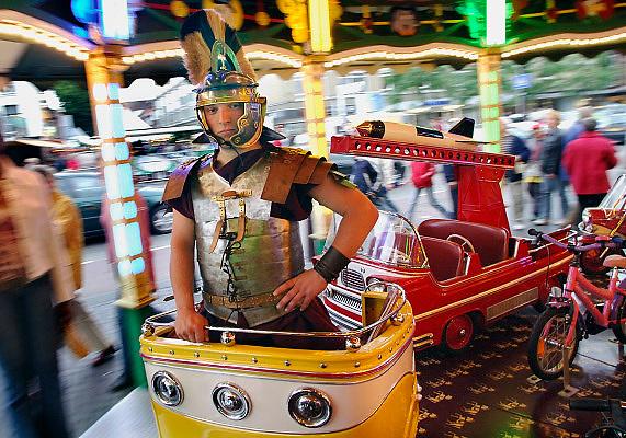 Nederland, Nijmegen, 23-7-2005..Een als Romein verklede werkstudent staat op een Romeinse strijdwagen van de draaimolen op de kermis tijdens de vierdaagse. Nijmegen bestond in 2005 2000 jaar, en liet deze historische figuuren door de stad lopen... Foto: Flip Franssen/Hollandse Hoogte