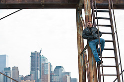 Man in a leather jacket with hands in his pockets hanging out on a metal staircase with a lower New York City skyline in the background
