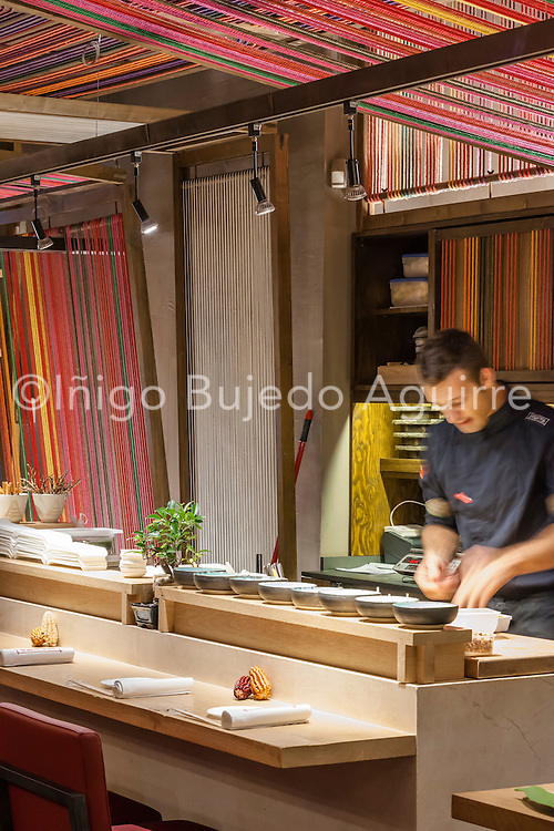 Patka Restaurant, Barcelona, Spain. Architect: El Equipo Creativo, 2013. View along bar counter with chef at work.