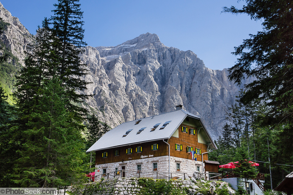 "At the end of the road in Vrata Valley, Slovenia, admire the close mountain grandeur of Triglav, Dolkova Spica, Skrlatica, and Stenar from Aljazev Dom hut [a dormitory refuge at 1015m elevation which serves meals, has 8 rooms with 23 beds, 115 communal beds; Tel: +386 (0)4 589 51 00 or +386 (0)4 589 10 30]. Walk easily 0.5 km to wide views at the ""Monument to fallen Partisans,"" and higher trails lead to steeper, technical routes. Mount Triglav (9396 feet) is the highest peak in the Julian Alps, which were named Julius Caesar, who founded some nearby cities. The scenic Vrata valley extends from Mojstrana village through a mixed forest of beech, spruce and fir, along crystal clear Triglavska Bistrica creek, to the north face of Triglav, in Triglavski narodni park, Slovenia's only national park. In 1991, Slovenia declared full sovereignty from Yugoslavia, in Europe. 80% of its 2 million people speak Slovene. In 2004, Slovenia joined NATO and the EU (European Union), and later adopted the Euro € currency. Slovenia is the richest Slavic nation per capita."