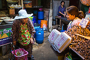 17 JANUARY 2013 - SAMUT SONGKHRAM, SAMUT SONGKHRAM, THAILAND: An elderly woman shops in the Samut Songkhram market. Four trains each day make the round trip from Baan Laem, near Samut Sakhon, to Samut Songkhram, the train chugs through market eight times a day (coming and going). Each time market vendors pick up their merchandise and clear the track for the train, only to set up again when the train passes. The market on the train tracks has become a tourist attraction in this part of Thailand and many tourists stop to see the train on their way to or from the floating market in Damnoen Saduak.    PHOTO BY JACK KURTZ