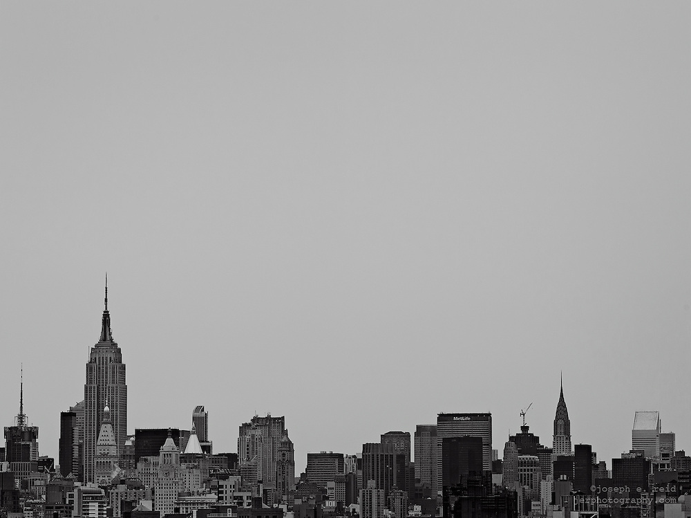Manhattan skyline including Empire State Building and Chrysler Buildling, seen from Brooklyn Bridge, New York, NY, US