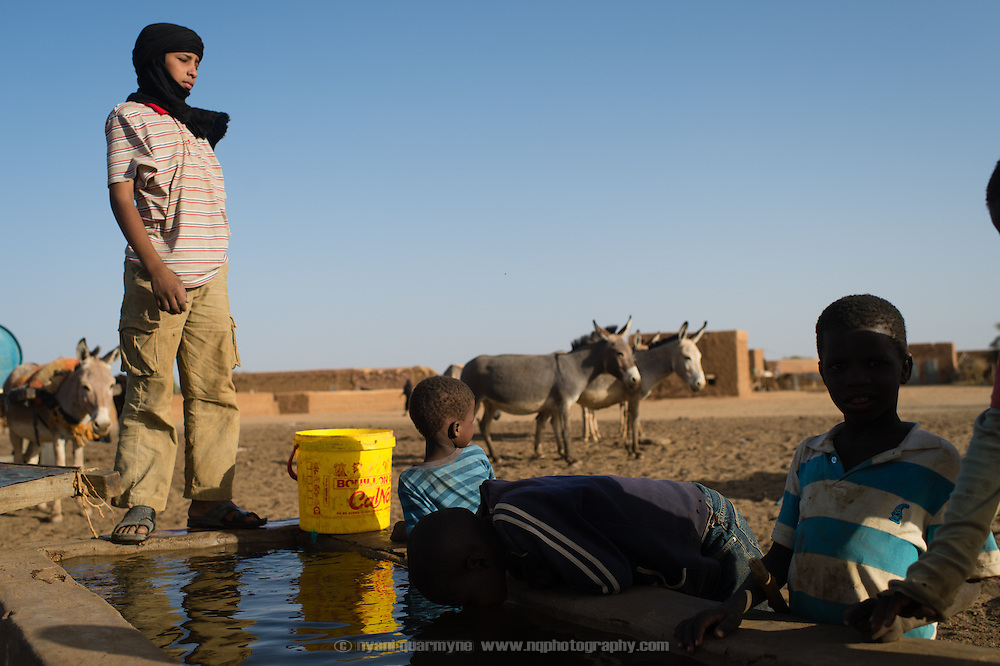 Children drink from a livestock trough at a well in Bassikounou, Mauritania on 7 March 2013. This appears to be a common practice for both children and adults, particularly as people report that the municipal water supply was non-functional at the time.