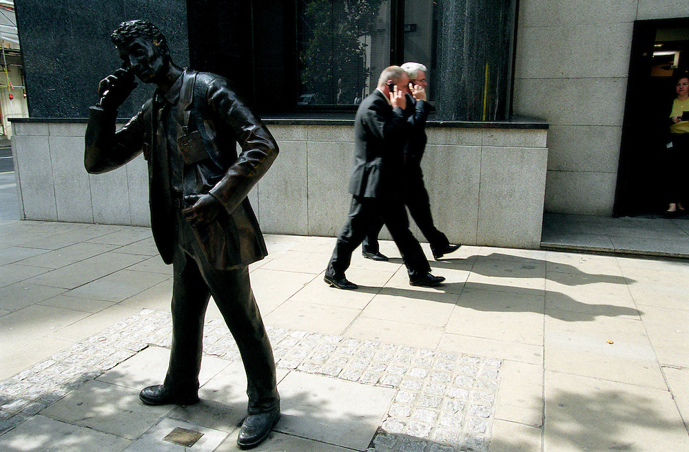 business men in the City of London on mobile phones walk past a statue of a city trader