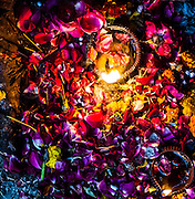 "15th January 2015, New Delhi, India. Flowers, petals, sweets and oil lamps left as offerings for wishes to be granted by Djinns in the ruins of Feroz Shah Kotla in New Delhi, India on the 15th January 2015<br /> <br /> PHOTOGRAPH BY AND COPYRIGHT OF SIMON DE TREY-WHITE a photographer in delhi. + 91 98103 99809. Email:simon@simondetreywhite.com<br /> <br /> People have been coming to Firoz Shah Kotla to leave written notes and offerings for Djinns in the hopes of getting wishes granted since the late 1970's. Jinn, jann or djinn are supernatural creatures in Islamic mythology as well as pre-Islamic Arabian mythology. They are mentioned frequently in the Quran  and other Islamic texts and inhabit an unseen world called Djinnestan. In Islamic theology jinn are said to be creatures with free will, made from smokeless fire by Allah as humans were made of clay, among other things. According to the Quran, jinn have free will, and Iblīs abused this freedom in front of Allah by refusing to bow to Adam when Allah ordered angels and jinn to do so. For disobeying Allah, Iblīs was expelled from Paradise and called ""Shayṭān"" (Satan).They are usually invisible to humans, but humans do appear clearly to jinn, as they can possess them. Like humans, jinn will also be judged on the Day of Judgment and will be sent to Paradise or Hell according to their deeds. Feroz Shah Tughlaq (r. 1351–88), the Sultan of Delhi, established the fortified city of Ferozabad in 1354, as the new capital of the Delhi Sultanate, and included in it the site of the present Feroz Shah Kotla. Kotla literally means fortress or citadel."