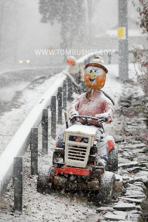 Middletown, New York - A scarecrow with a pumpkin head sits on riding lawn mower during a snowstorm on Oct. 29, 2011.