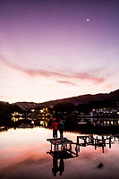 Casal sobre deck na Lagoa da Conceição ao anoitecer. Florianópolis, Santa Catarina, Brasil. / Couple on a deck at Conceicao Lagoon at dusk. Florianopolis, Santa Catarina, Brazil.