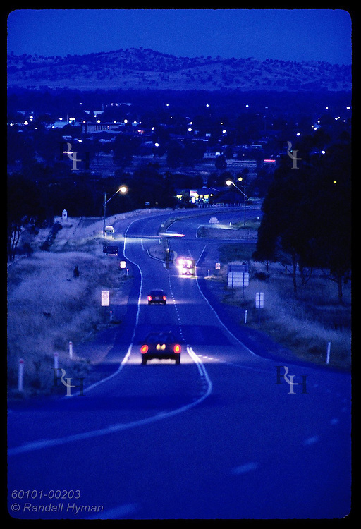 Car lights cut through the dusk on highway into agricultural town of Wagga Wagga; (v) NSW. Australia