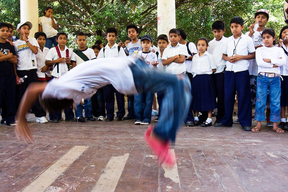 School children watch a break dancing and back flipping display in the band stand in the town square after school in the town square before going home. Granada, Nicaragua. Granada is Nicaragua's most famous city. founded in 1524 it is one of best examples of Spanish colonial architecture in the Americas. .it has a varied history including its almost total destruction by filibuster William Walker in a childlike tantrum. Today it is a popular tourist town though retains a strong sense of its own identity.