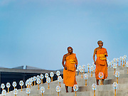 "11 FEBRUARY 2016 - KHLONG LUANG, PATHUM THANI, THAILAND: Buddhist monks walk to their seat during the Makha Bucha Day service at Wat Phra Dhammakaya.  Makha Bucha Day is a public holiday in Cambodia, Laos, Myanmar and Thailand. Many people go to the temple to perform merit-making activities on Makha Bucha Day, which marks four important events in Buddhism: 1,250 disciples came to see the Buddha without being summoned, all of them were Arhantas, or Enlightened Ones, and all were ordained by the Buddha himself. The Buddha gave those Arhantas the principles of Buddhism. In Thailand, this teaching has been dubbed the ""Heart of Buddhism."" Wat Phra Dhammakaya is the center of the Dhammakaya Movement, a Buddhist sect founded in the 1970s and led by Phra Dhammachayo. Makha Bucha Day is one of the most important holy days on the Thai Buddhist calender.      PHOTO BY JACK KURTZ"