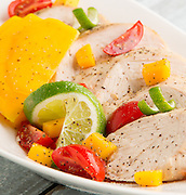Southwest inspired Chicken breast garnished with lime zest, mangos, and cherry tomatoes