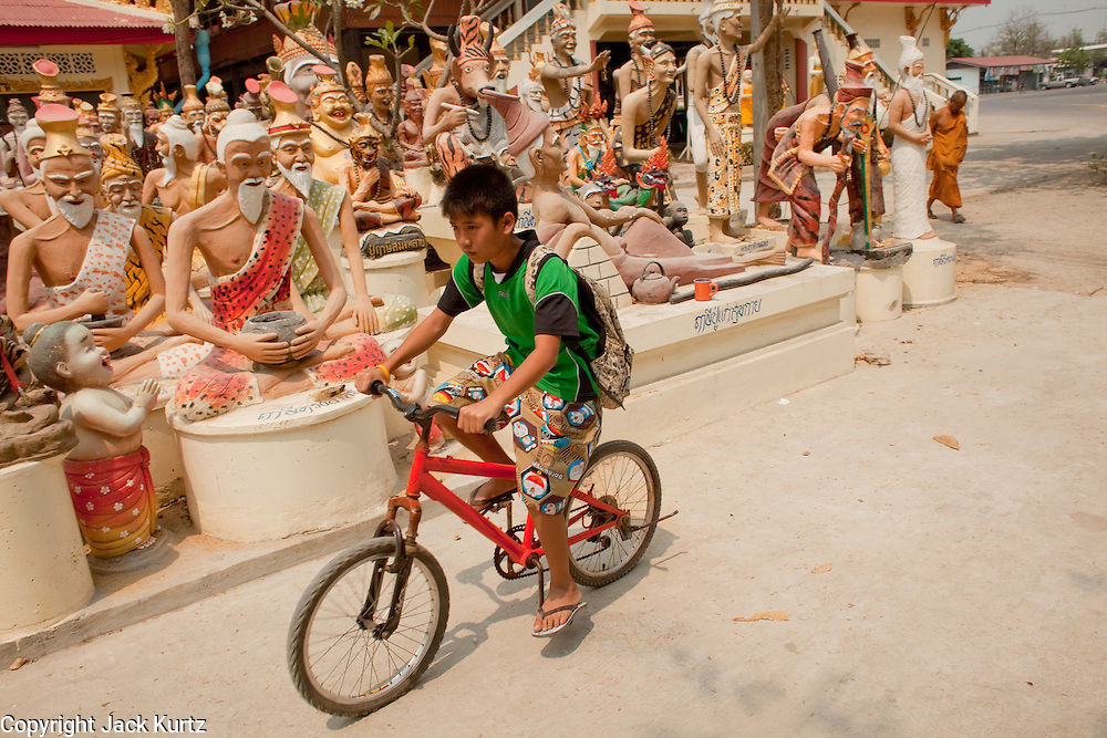 "Mar. 29, 2010 - NAKORN CHAI SRI, THAILAND:   A boy rides his bike into Wat Bang Phra about 30 miles from Bangkok in Nakhon Pathom province. The temple is famous for its tattooing monks who give people ""Sak Yent"" tattoos, a form of sacred tattooing practiced in Southeast Asian countries including Cambodia, Laos, and Thailand.   PHOTO BY JACK KURTZ"