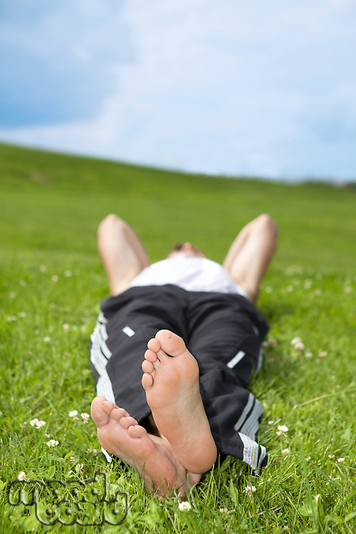 Young man lying on grass in park