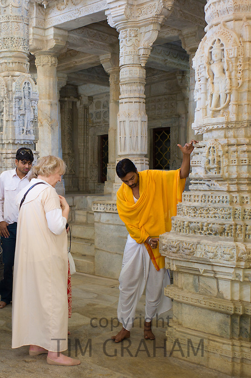 Temple priest shows tourists stone carving detail at The Ranakpur Jain Temple at Desuri Tehsil in Pali District of Rajasthan, India