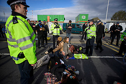 "© Licensed to London News Pictures. 19/11/2016. Heathrow, UK. An activist wearing the slogan ""NO NEW RUNWAY"" sits on the road surface, that she and other activists are attached to, near Heathrow Airport. A group of activists stage attach themselves to a road surrounding  Heathrow Airport, during a demonstration against the expansion of Heathrow Airport and the building of a third runway. Some activists  threatened ""direct action"". Photo credit: Ben Cawthra/LNP"
