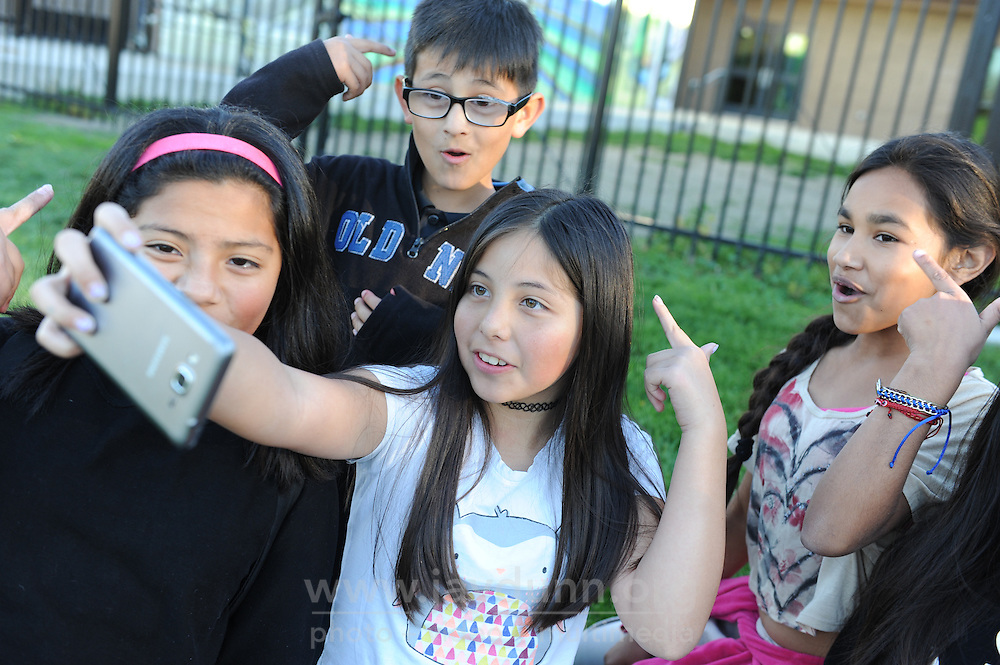 From left, Evelyn Godoy, 10, Nathan Watkins, 8, Jasmin Gonzalez, 10 and Maria Jimenez, 10, make a video using Musical.ly on the lawn behind the Chávez Library in east Salinas.
