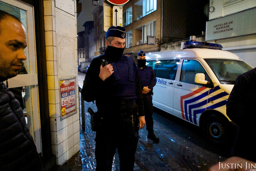 People gather to watch police action in Brussels' Molenbeek neighbourhood, a hotbed of Islamic fundamentalism.