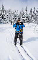 A woman making pictures with her camera while cross country skiing in a forested setting.